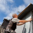 Stock Photo: Roofer assemble metal piece into dormer wall