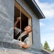 Stock Photo: Roofer taking measures for a new window