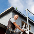 Smiling roofer climbing a ladder — Stock Photo