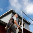 Roofer climbing a ladder into the scaffolding — Stock Photo