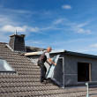 Roofer carrying a metal piece to the dormer — Stockfoto
