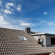View of a rooftop with a working roofer — Stockfoto