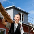 Roofer carrying a wood plank over his shoulder — Stock Photo