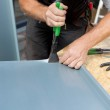 Roofer folding a metal sheet using special pliers — Stock Photo #28284075