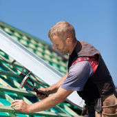 Roofer hammering nails into beams — Stock Photo