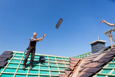 Two roofers tossing tiles — Stock Photo