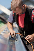 Mature roofer applying weld into the gutter — Stock Photo