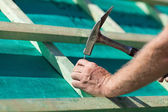 Roofer hammering a nail on the roof beams — Stock Photo