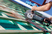 Close-up of a roofer using a hand circular saw — Stock Photo