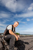 Smiling roofer sitting on the rooftop — Stock Photo