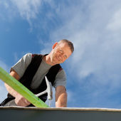 Smiling roofer hammering a nail — Stock Photo