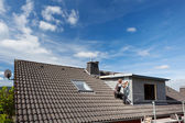 View of a rooftop with a working roofer — Stock Photo