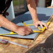 Roofer working with a protractor on a metal sheet — Stock Photo