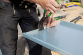 Roofer folding a metal sheet using special pliers — Stock Photo
