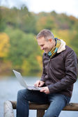 Man Using Laptop While Sitting On Fence — Stock Photo