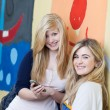 Two beautiful schoolgirls with a mobile phone — Stock Photo