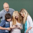Schoolchildren playing with a mobile phone — Stockfoto