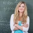Photo: Confident female student in maths class