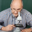 Man looking down a microscope — Stockfoto