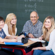 Smiling teacher and students in a group activity — Stock Photo #28817219