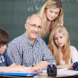Male teacher surrounded by his pupils — Stock Photo