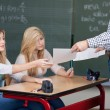 Stock Photo: Teacher handing out marked assignments
