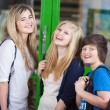 Three cheerful students standing chatting — Stock Photo
