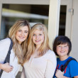 Three young students in front of the school — Stock Photo