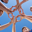 Children And Teacher Forming Hearts Against Blue Sky — Stock Photo