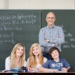 Stock Photo: Confident Professor And Students Smiling Together Against Chalkb