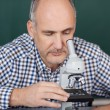 Professor Looking Through Microscope In Science Class — Stock Photo #28819649