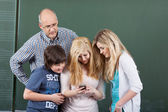 Schoolchildren playing with a mobile phone — Stock Photo
