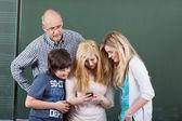 Школьников, играя с мобильного телефона — Стоковое фото