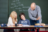 Two students being helped by a teacher — Stock Photo