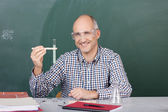Laughing science teacher holding up a test tube — Stock Photo