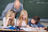 Three school pupils in class with a teacher — Stock Photo