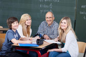 Smiling teacher and students in a group activity — Stock Photo