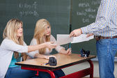 Teacher handing out marked assignments — Stock Photo