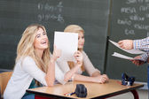 Happy student with her marked assignment — Stock Photo