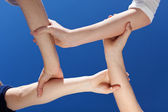 Closeup Of Friends Holding Hands Against Clear Blue Sky — Stock Photo