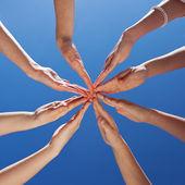 Studenti a učitele ruce společně proti obloze — Stock fotografie