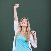 Flicka med arm höjt firar seger mot svarta tavlan — Stockfoto