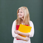 Thoughtful Teenage Girl Holding Files Against Chalkboard — Stock Photo