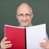 Professor Holding Book Against Chalkboard — Stock Photo