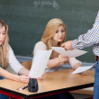 Professor Giving Exam Papers To Nervous Students At Desk — Stock Photo #28820309