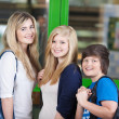 Stock Photo: Happy Students Standing Against Door In School