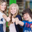 Happy Students Showing Thumbs Up Sign Together In School — Stock Photo #28820863
