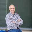 Professor With Arms Crossed Sitting On Desk — Stock Photo #28820957