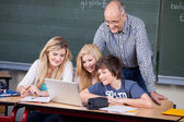 Students Using Laptop While Professor Looking At It At Desk — Stock Photo