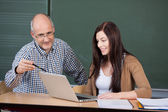 Professor Assisting Woman In Using Laptop Against Chalkboard — Stock Photo